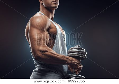 Young Man With Dumbbell Prepare To Flexing Muscles Over Dark Background