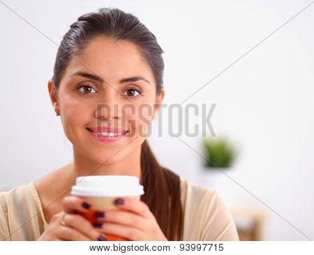 Beautiful  businesswoman enjoying coffee in bright office, sitting