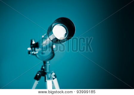 telescope on blue background with copy-space