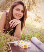 foto of haystack  - portrait of a pretty girl with a magazine and a bouquet of daisies on a background of haystacks - JPG
