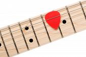 picture of fret  - Empty wooden maple fingerboard with red pick between strings of classic shaped electric guitar closeup isolated on white background with clipping path - JPG