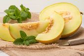 stock photo of muskmelon  - Juicy honeydew melon on a wooden table background - JPG