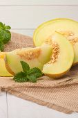stock photo of honeydew melon  - Juicy honeydew melon on a wooden table background.
