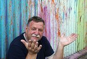 image of 55-60 years old  - Mature mustachioed man sitting against the wall - JPG