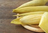 foto of corn  - Corn and sticky corn placed on a wooden table - JPG