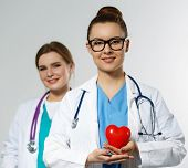 picture of heart surgery  - Beautiful smiling female doctor holding red heart in front of chest - JPG