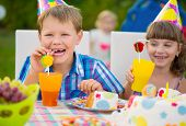 stock photo of birthday hat  - Modern birthday party with colorful cake at backyard