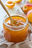 image of apricot  - Apricot jam in a glass jar apricots and linen napkin on wooden background - JPG
