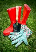 stock photo of spade  - Closeup shot of small spade gloves and red rubber boots lying on green grass - JPG