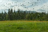 stock photo of rain-drop  - View of the mountain landscape with forest meadow and flowers through the window glass of the car covered by rain drops - JPG