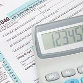 stock photo of cpa  - Calculator over US 1040 Tax Form  - JPG