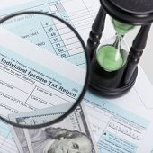 image of cpa  - USA 1040 Tax Form with magnifying glass and hourglass  - JPG
