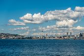 foto of puffy  - White puffy clouds hover over the Seattle skyline on a sunny day - JPG