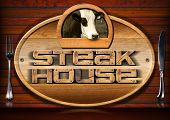 stock photo of oval  - Oval wooden sign with text Steak House head of cow and silver cutlery on a brown wooden wall - JPG