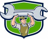 pic of overalls  - Illustration of a mechanic wearing hat and overalls looking to the side lifting giant spanner wrench viewed from front set inside shield crest on isolated background done in cartoon style - JPG