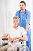 foto of male nurses  - Kind male nurse taking care about senior patient in wheelchair at clinic - JPG