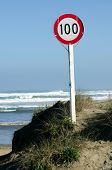 stock photo of mile  - A 100 km speed limit sign on Ninety Mile Beach in Northland New Zealand - JPG