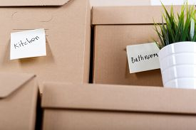 stock photo of packing  - Pile of brown cardboard boxes with house or office goods - JPG