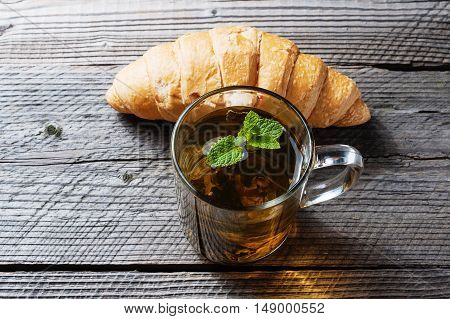 breakfast with fresh croissants and tea on wooden desk