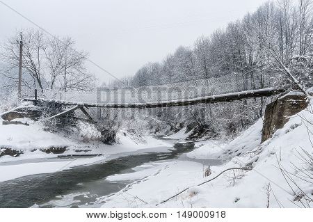 Suspended wooden bridge over a winter mountain river. Karpaty Ukraine