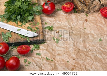 Kitchen background with baking paper tomatoes and parsley