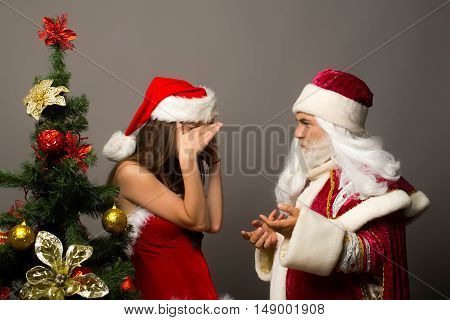 Shy pretty girl in new year dress hides face with hands from santa claus near Christmas tree