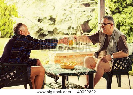 Two senior friends enjoying and drinking beer.
