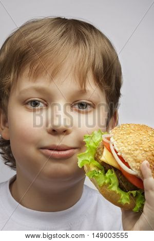 Happy boy with burger. Teenager with a delicious sandwich on a white background