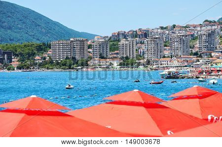 Herceg Novi, red sunshades, blue sea and modern town, Montenegro