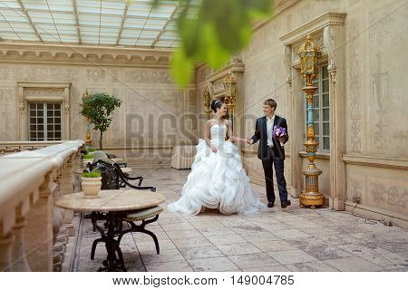 Wedding couple is walking. Beautiful model girl in white dress. Handsome man in suit. Beauty bride with groom. Female and male portrait. Woman with lace veil. Lady and guy indoors