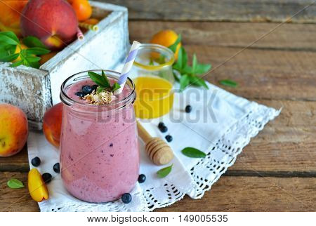 Smoothie of peach banana and blueberries with oats on a wooden background