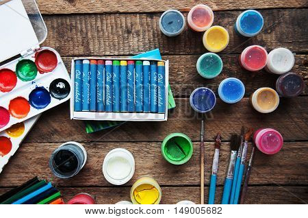 Art of Painting. Paint buckets on wood background. Different paint colors painting on wooden background. Painting set: brushes paints crayons chalk watercolor acrylic paint on a wooden background