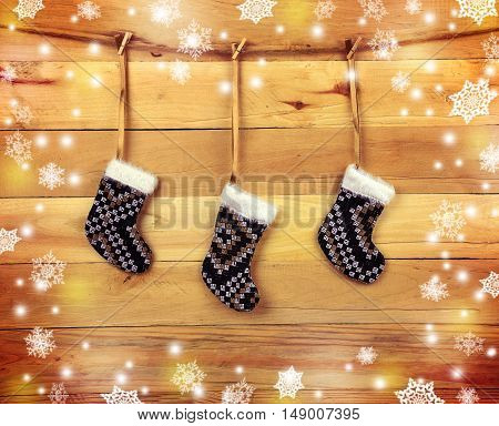 Decorative handmade socks on the old wooden background. Village stil.Ogni and snowflakes. Winter. Children's expectations. Nostalgia.