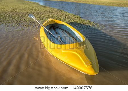 A yellow kayak lies on the bank by the water on an early summer morning.