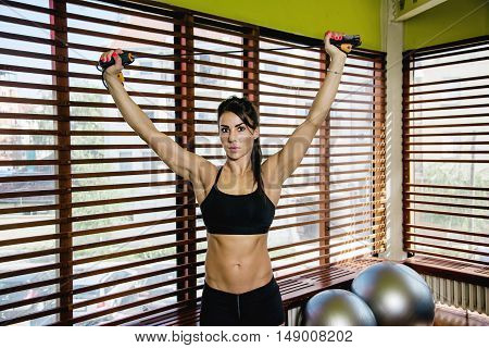 Young sporty woman with gymnastics skipping rope