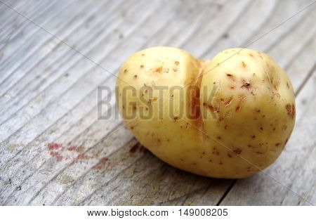 Potatoes in the form of heart on a wooden table