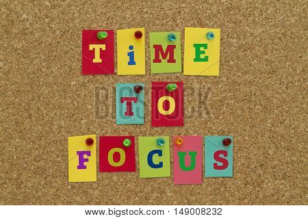 TIME TO FOCUS message written on colorful sticky notes pinned on cork board.