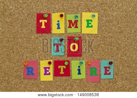 TIME TO RETIRE message written on colorful sticky notes pinned on cork board.