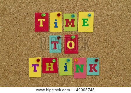 TIME TO THINK message written on colorful sticky notes pinned on cork board.