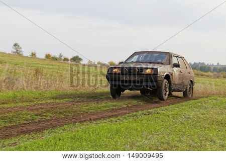 Dirty Rally Car Racing On The Road Among Fields.