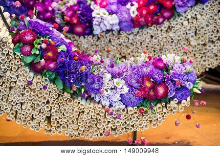 beautiful decoration floral composition or bouquet of seasonal chrysanthemum and eustoma flowers violet and purple colors with dogrose on bamboo sticks in arc shape