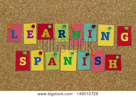Learning Spanish word written on colorful notes pinned on cork board.