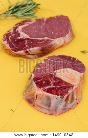Two pieces of raw meat of pork on a cutting board yellow with a green leaves