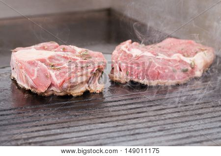Two pieces of raw meat are fried on a black electric grill that smokes