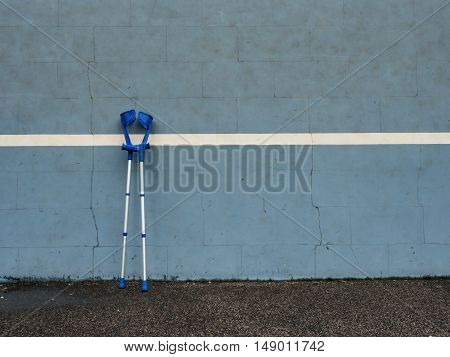 Medical Crutch At Blue Training Tennis Wall  On Outdoor Stadium Players Court,