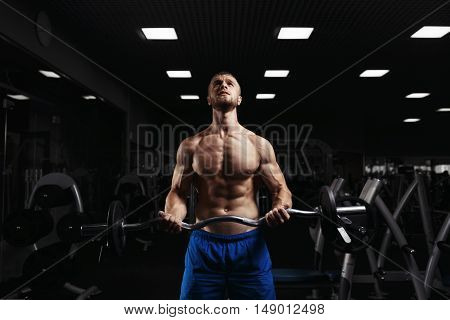 Muscular man working out in gym doing exercises with barbell at biceps, strong male naked torso abs. Muscular bodybuilder doing exercise with barbell. Bodybuilder in the gym