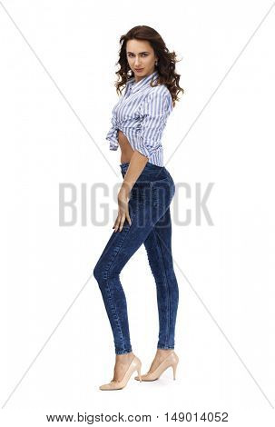 Young beautiful brunette woman in blue jeans and striped shirt, isolated on white