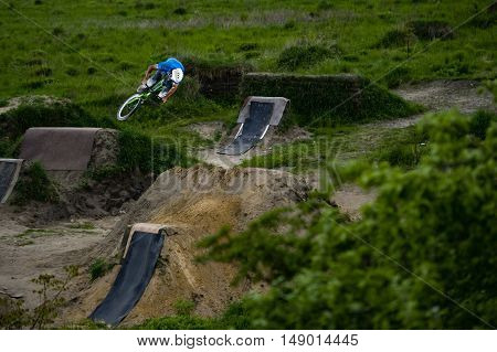 Dirt cyclist jumping trick on the track
