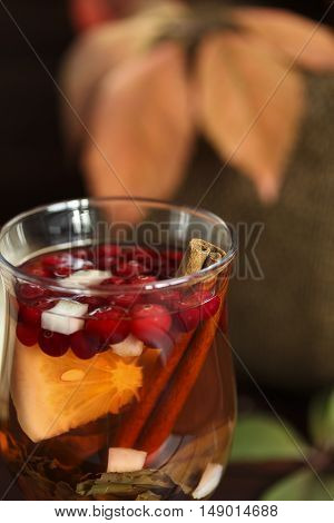 Autumn hot tea with lemon spices in glass cup falling leaves around macro
