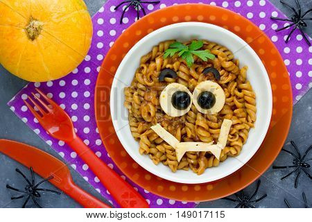 Funny and creative idea recipe Halloween food for kids - fusilli pasta with sauce bolognese shaped cute vampire monster face top view
